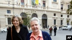 FILE - Marie Collins, right, who was assaulted as a 13-year-old by a hospital chaplain in her native Ireland, is flanked by British psychiatry professor Sheila Hollins, as they arrive at a Vatican-backed symposium on clerical sex abuse, in Rome, Feb. 7, 2