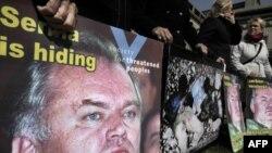 """Demonstranti ispred Haškog tribunala nose plakate sa sloganom """"Srbija skriva ratnog zločinca Ratka Mladića"""", u aprilu 2010."""