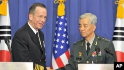 U.S. Navy Adm. Mike Mullen, left, the U.S. chairman of the Joint Chiefs of Staff, and South Korean Gen. Han Min-Koo, right, chairman of South Korean Joint Chiefs of Staff shake hands after their joint press conference at the Defense ministry in Seoul, De