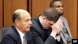 Cleveland police officer Michael Brelo, center, listens to the judge reading his verdict during his trial in Cleveland, Ohio, May 23, 2015.