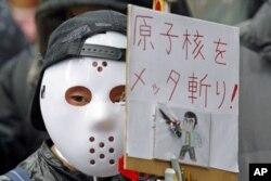 ដោយពាក់មុខផង អ្នកតវ៉ាម្នាក់កាន់ផ្លាកសញ្ញានៅកន្លែងតវ៉ាមួយនៅមុខទីស្នាក់ការក្រុមហ៊ុនថាមពលអគ្គីសនីតូក្យូ Tokyo Electric Power Company [TEPCO] ដោយរិះគន់ដល់ក្រុមហ៊ុននេះ និងទាមទារឲ្យបំបាត់ថាមពលនុយក្លេអ៊ែរ ក្នុងរដ្ឋធានីតូក្យូ ថ្ងៃទី៣ មិនា ២០១