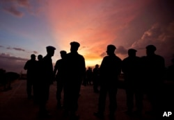 FILE - This photo shows silhouettes of U.N. peacekeepers from Brazil at the airport in Port-au-Prince, Haiti, July 11, 2011. According to an AP investigation, some 150 allegations of abuse and exploitation were reported in Haiti between 2004 and 2016. The allegations involved U.N. peacekeepers and other personnel.
