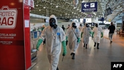 FILE - Navy soldiers are seen after carrying out a disinfection operation against the novel coronavirus COVID-19 at Tom Jobim Galeao International Airport in Rio de Janeiro, Brazil, on April 24, 2020.