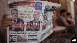 یک تونسی روزنامه ای میخواند که از پیشتازی قیس سعید و نبیل قروی با عنوان زلزله سیاسی یاد کرده است.