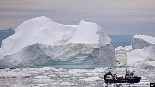 A fishing boat weaves through icebergs shed from the Greenland ice sheet, near Ilulissat, Greenland, July 18, 2011.