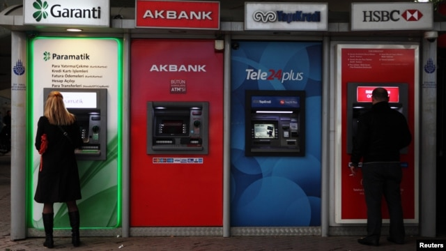 FILE - People withdraw Turkish liras from automatic teller machines in Istanbul, October 17, 2011.
