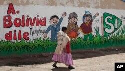 """ແມ່ຍິງຊົນເຜົ່າ Aymara ຄົນໜຶ່ງກຳລັງຍ່າງຜ່ານຝາທີ່ມີຕົວ ໜັງສືຂຽນເປັນພາສາ ສເປນ """"Tell Bolivia Yes,"""" ຫຼື """"ບອກ ໂບລີເວຍວ່າ ແມ່ນ"""" ໃນການສະໜັບສະໜູນປະທານາທິ ບໍດີ ທ່ານ Evo Morales, ໃນເມືອງ El Alto, ປະເທດ ໂບລີເວຍ, 20 ກຸມພາ, 2016."""