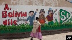 """Seorang perempuan melewati lukisan dinding bertuliskan """"Katakan pada Bolivia Ya,"""" dalam bahasa Spanyol, mendukung Presiden Evo Morales, di El Alto, Bolivia, 20 Februari 2016."""