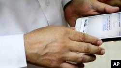 FILE - Human rights activist Ahmed Mansoor shows Associated Press journalists a screenshot of a spoof text message he received in Ajman, United Arab Emirates, Aug. 25, 2016. Mansoor was recently targeted by spyware that can hack into Apple's iPhone.