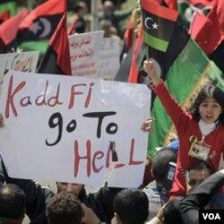 Warga di Benghazi melakukan unjuk rasa dengan membawa berbagai poster anti-Gaddafi.