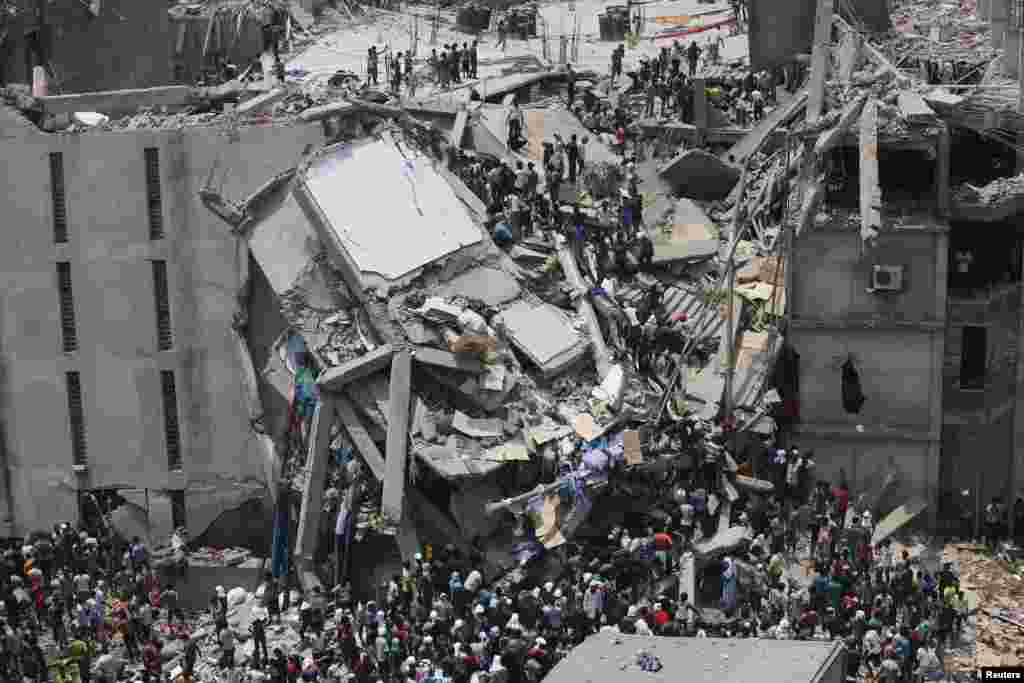 People rescue garment workers trapped under rubble at the Rana Plaza building after it collapsed, in Savar, 30 km (19 miles) outside Dhaka, Bangladesh. An eight-story block housing garment factories and a shopping center collapsed on the outskirts of the capital, killing nearly 100 people and injuring hundreds.