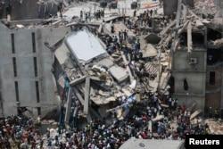 Petugas menyelamatkan para pekerja yang terperangkap di bawah reruntuhan gedung Rana Plaza di Savar, Bangladesh, 24 April 2013.