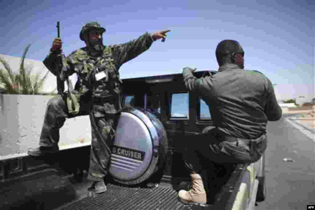 Rebel fighters talk to each other at the town of Brega, Libya, Monday, Aug. 15, 2011. Most of the town has been liberated from Moammar Gadhafi's forces, with fights going on only at the oil terminal, according the rebel military spokesman, Ahmed Bani (AP