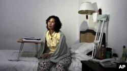 Bà Nghê Ngọc Lan ngồi trên giường trong một khách sạn ở Bắc Kinh.