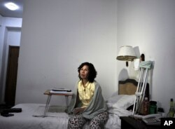 FILE - Chinese Human rights activist Ni Yulan sits on the bed in a hotel in Beijing. She has been barred by Beijing from traveling to Washington.