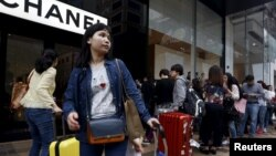 FILE - Mainland Chinese visitors wait outside a luxury store at a shopping district in Hong Kong.