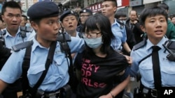 A protester is taken away by police officers after the confrontation between activists demonstrating against mainland Chinese shoppers and local villagers at a suburban district of Yuen Long in Hong Kong, Sunday, March 1, 2015.