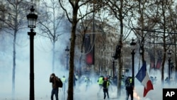 "Demonstrators run away through tear gas during scuffles on the Champs-Elysees, Dec. 15, 2018, in Paris. Protests throughout the day against France's high cost of living by ""yellow vest"" demonstrators were largely peaceful."
