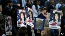 Des habitants tiennent des panneaux avec la photo d'une victime du 11 septembre à ground zero à New York, le 11 septembre 2017.