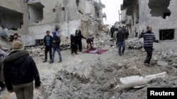 FILE - Residents inspect a crater at a site hit by what activists said were three consecutive air strikes carried out by the Russian air force, the last which hit an ambulance, in the rebel-controlled area of Maaret al-Numan town in Idlib province, Syria.