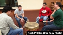 Native American students drum and sing together in a ceremony at the University of Wisconsin-Madison.