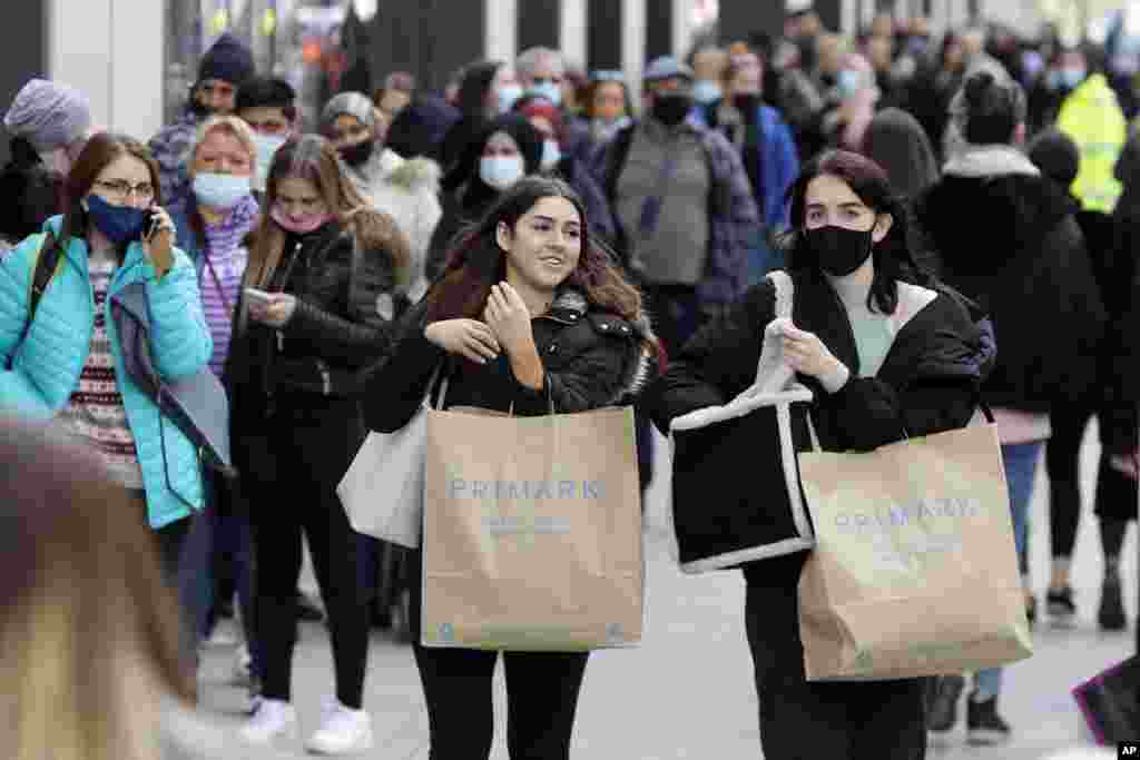People carry shopping bags while others queue to enter a store on Oxford Street in London. Millions of people will get their first chance in months for haircuts, casual shopping and restaurant meals, as the government takes the next step on its lockdown-lifting road map.