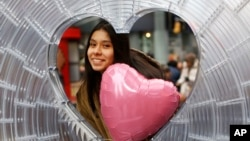 "Karina Sosa, 15, of Asuncion Paraguay, poses for a photograph at ""Window to the Heart,"" a Valentine's Day themed art installation in Times Square, Thursday, Feb. 1, 2018, in New York. (AP Photo/Kathy Willens)"