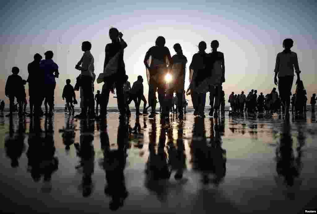 People walk on a beach along the shores of the Arabian Sea in Mumbai, India.