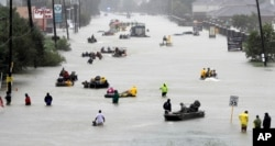 FILE - Rescue boats float on a flooded street as people are evacuated from rising floodwaters brought on by Tropical Storm Harvey on Aug. 28, 2017, in Houston, Texas.