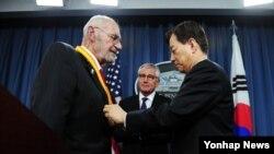 한민구 한국 국방부 장관(오른쪽)이 23일 미국 워싱턴 국방부에서 한국전 참전용사인 윌리엄 웨버 미국 육군 예비역 대령에게 '백선엽 한미동맹상'을 수여하고 있다.