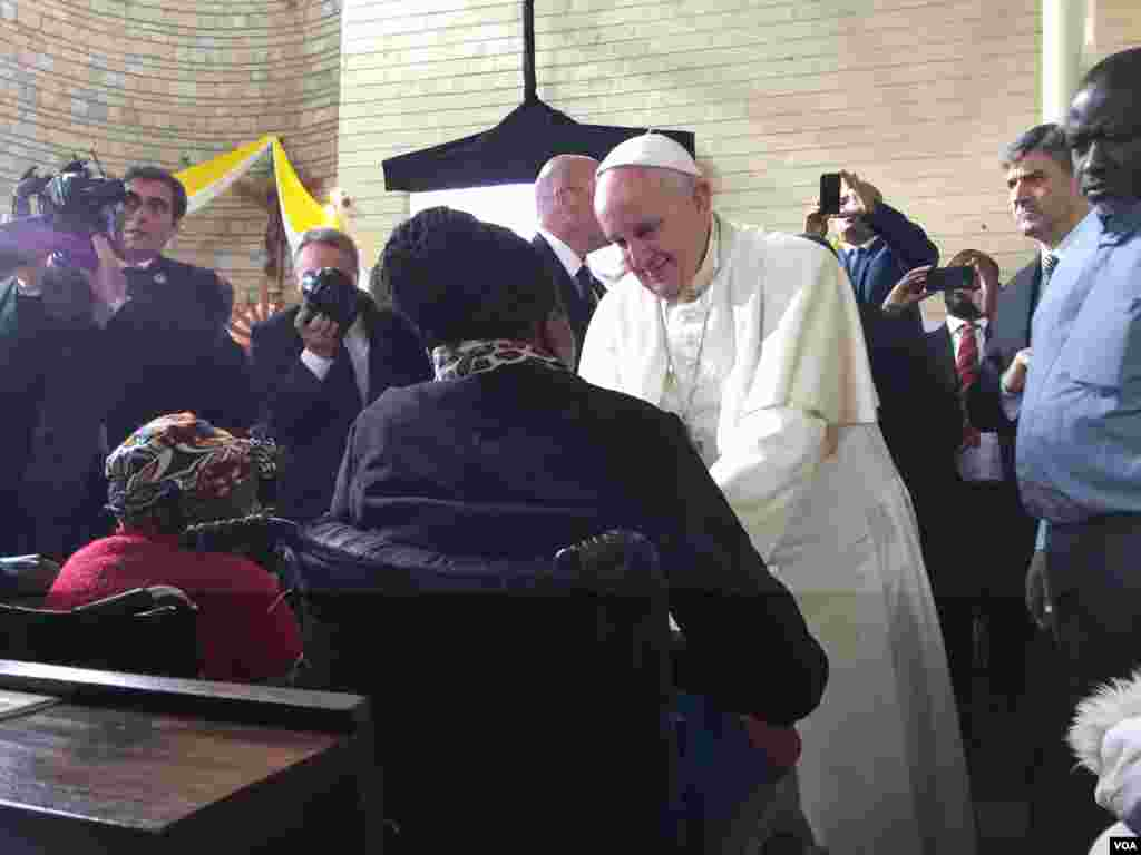 The Pope greeting a woman in a wheelchair at the event in Kangemi, Nov. 27, 2015. (J. Craig/VOA)