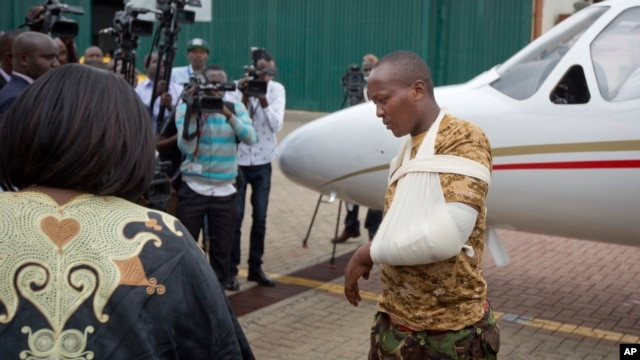 A Kenyan soldier, who Kenya Defence Forces said was injured in the attack by al-Shabab in Somalia, walks from an airplane to a waiting ambulance after being airlifted back to Nairobi for medical treatment, Jan. 17, 2016.