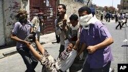 부상한 동료를 대피시키는 시위대원들