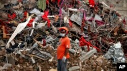 A Bangladeshi rescuer stands amid the rubble of a garment factory building that collapsed on April 24 as they continue searching for bodies in Savar, near Dhaka, Bangladesh, May 12, 2013.
