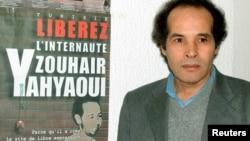 Le juge Mokhtar Yahyaoui pose devant une affiche publicitaire à Tunis le 7 février 2003, après une réunion tenue pour libérer son neveu, Zouhair Yahyaoui, qui a été arrêté en mai 2002.