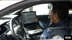 Arlington County Police Officer Patrice Malone checks the computer in her cruiser. (Mike Burke/VOA)