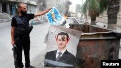 Một thành viên của quân đội Giải phóng Syria chuẩn bị vứt tấm hình cha của Tổng thống Bashar al-Assad vào thùng rác ở thành phố Aleppo.