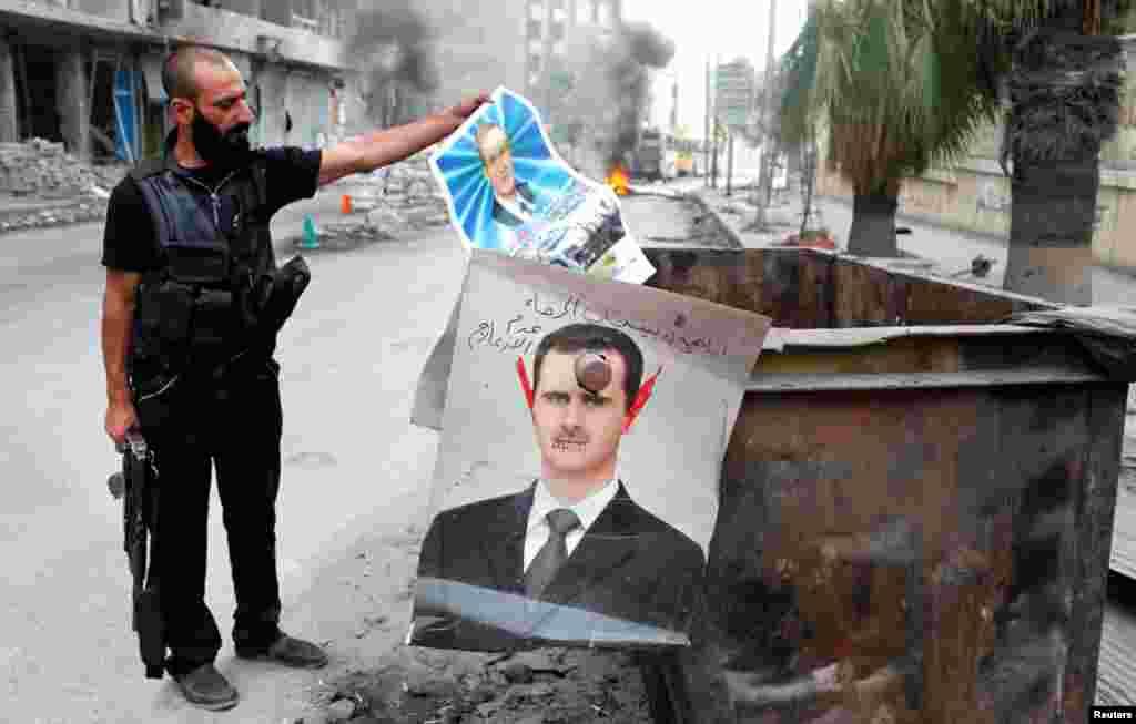시리아 알레포에서 알-아사드 대통령의 포스터를 훼손하고 있는 반군