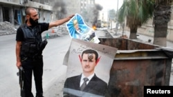 A member of the Free Syrian Army holds up a poster of Hafez al-Assad, the father of current President Bashar al-Assad whose defaced picture is seen hanging on a garbage bin near an area that they set fire to in the city of Aleppo, October, 17, 2012.