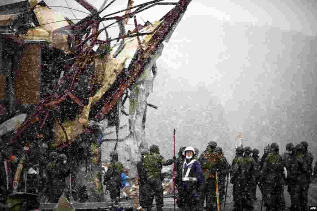 Начался крупный снег в то время когда группа японских сил самообороны прибыла в когда то жилой район Отсучи, Япония, 16 марта 2011г.