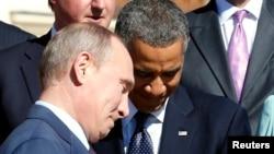 Russian President Vladimir Putin (L) walks past U.S. President Barack Obama (C) during a group photo at the G20 Summit in St. Petersburg September 6, 2013.