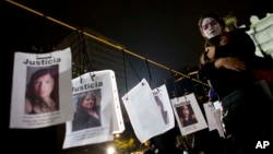 People hug next to images of murdered women following a Day of the Dead march calling for justice for victims of femicide, in Mexico City, Nov. 1, 2017.