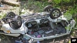 Mobil van yang terjungkal di kawasan kebun binatang Bronx, kota New York, Minggu (29/4).