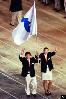 FILE - In this Sept. 15, 2000, file photo, Pak Jung Chul, left, a North Korea's Judo coach, and Chung Eun-sun, a South Korean basketball player, carry a flag representing a united Korea into Olympic Stadium during the Opening Ceremony of the Olympics.