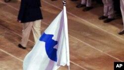 Trong ảnh tư liệu ngày 15/9/200 này: Pak Jung Chul (trái), huấn luyện viên Judo của Triều Tiên, và Chung Eun-sun, cầu thủ bóng rổ Hàn Quốc cùng mang lá cờ thống nhất Triều Tiên dẫn hai đoàn thể thao của hai miền Triều Tiên diễu hành chung tại lễ khai mạc Olympic Sydney 2000.
