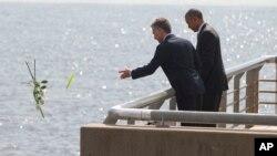 Presiden AS Barack Obama (kanan) mengamati Presiden Argentina Mauricio Macri melemparkan bunga ke sungai saat mengunjungi Parque de la Memoria (Taman Peringatan) di Buenos Aires, Argentina, Kamis (24/3).