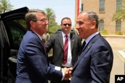 FILE - Visiting U.S. Defense Secretary Ash Carter, left, shakes hands with Iraqi Defense Minister Khaled al-Obeidi at the Ministry of Defense, Baghdad, Iraq, July 11, 2016.