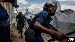 FILE - Burundi's policemen and army forces run after protesters against incumbent president Pierre Nkurunziza's bid for a 3rd term on May 13, 2015 in Bujumbura, May 13, 2015. Officials in Burundi say at least five people were killed and six injured when gunmen opened fire on a market Monday evening.