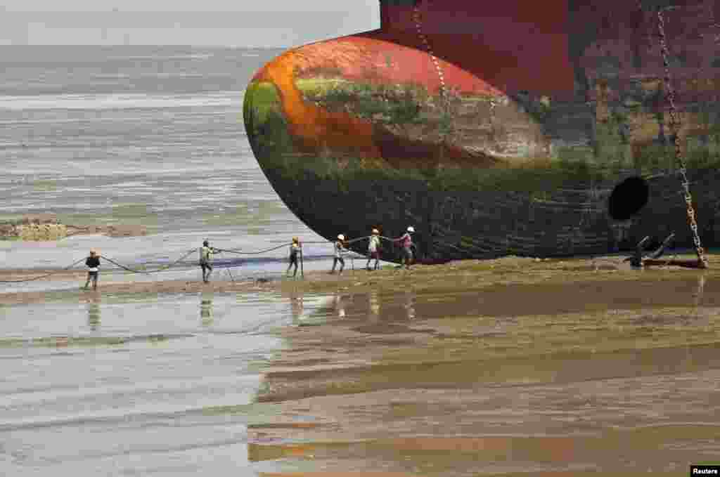 Workers carry a rope to a decommissioned ship at the Alang shipyard in the western Indian state of Gujarat.