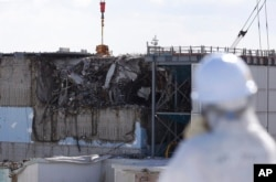 FILE - A member of a media tour group wearing a protective suit and a mask looks at the No. 3 reactor building at Tokyo Electric Power Co.'s tsunami-crippled Fukushima Daiichi nuclear power plant in Okuma, Japan, Feb. 10, 2016.